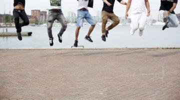 Kuusi alaikäisiä turvapaikanhakijaa hyppää ilmaan, kuvassa ei näy kasvoja.