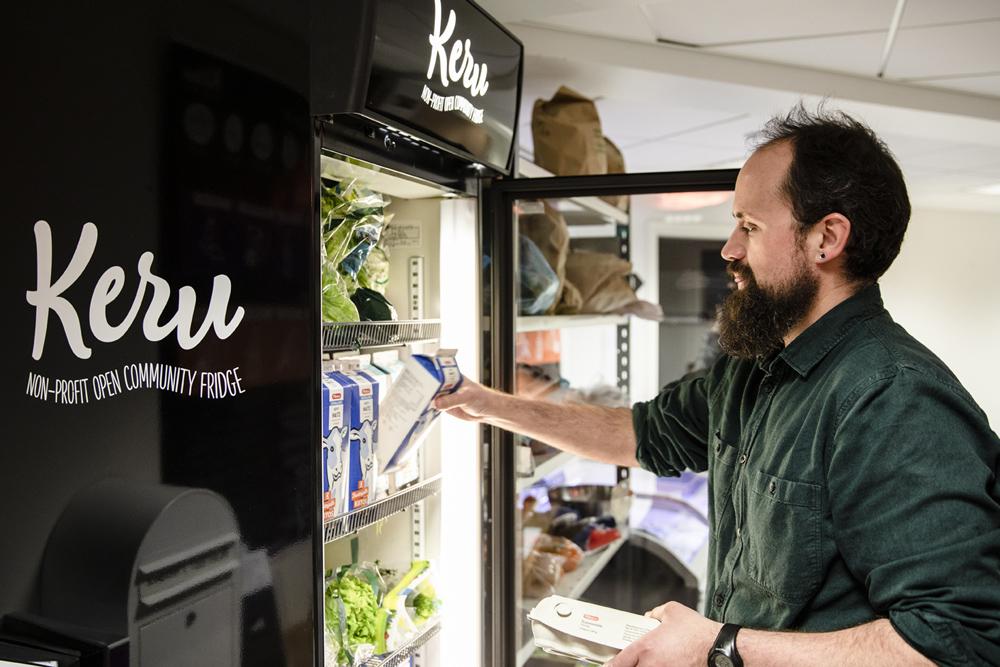 Yhteisöjääkaappi, josta parrakas mies ottaa ruokaa
